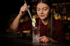Barman de femme faisant un cocktail frais avec le genièvre et le concombre images libres de droits