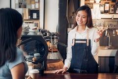 Barman de femme parlant avec le client sur goûté de la tasse de café avec émotion heureuse à la contre- barre au café owne d'affa photographie stock libre de droits