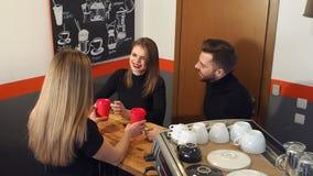 Barman de sorriso da menina que dá a bebida a um par que senta-se perto do contador da barra no café video estoque