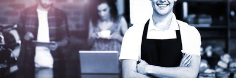 Barman de sourire avec des bras croisés devant des clients photographie stock libre de droits