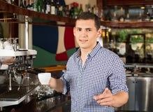 Barman de sourire beau tenant une tasse de café et dirigeant le fi image libre de droits