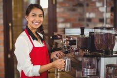 Barman de sourire cuisant le lait à la vapeur à la machine de café image libre de droits
