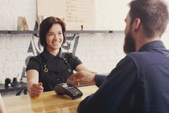 Barman de sourire prenant le paiement du client au café photo libre de droits