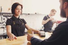 Barman de sourire prenant le paiement du client au café images libres de droits