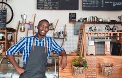 Barman de sourire se penchant sur le compteur dans un café images stock