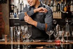 Barman de sourire se tenant derrière le compteur de barre avec un équipement de barre image stock