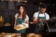 Barman de sourire tenant des sandwichs et faire le café image libre de droits