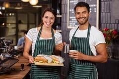 Barman de sourire tenant les sandwichs et le lait chaud Images libres de droits