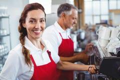 Barman de sourire utilisant la machine de café avec le collègue derrière Photographie stock libre de droits