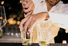 Barman is decorating a cocktail with lime yo Stock Photos