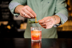 Barman dekoruje koktajl z pomarańczowej łupy i rozmarynów zamknięty up Zdjęcia Stock