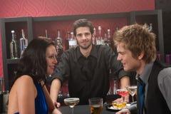 Barman derrière les amis de bar ayant la boisson photos libres de droits