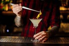 Barman die aan een Witte oranje schil van de Damecocktail toevoegen royalty-vrije stock afbeeldingen