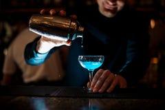 Barman die blauwe cocktail voorbereiden bij cocktailglas bij de bar Royalty-vrije Stock Afbeelding