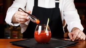 Barman die Bloody mary of Caesar-cocktail verfraaien bij de bar stock afbeelding