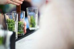 Barman die cocktail voor gasten voorbereiden stock afbeelding