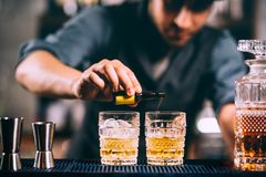 Barman die cocktailingrediënten op whiskycocktails toevoegen bij de bar stock foto