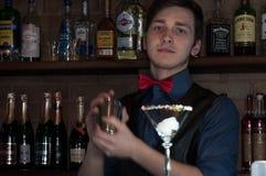 Barman die drank met sheker maken bij teller met glas in bar stock afbeelding