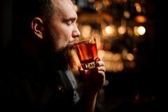 Barman die een cocktail in het glas met een oranje schil proeven als decor royalty-vrije stock afbeelding