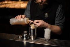 Barman die een heerlijke alcoholische drank van het staal jigger en essentie gieten stock afbeelding