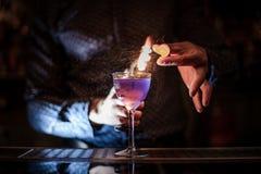 Barman die een sterke purpere de zomercocktail met een rooknota maken Stock Afbeelding