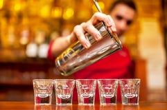 Barman die en de zomer alcoholische cocktails mengen gieten Stock Afbeeldingen