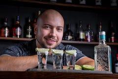 Barman die harde geest gieten in kleine glazen zoals alcoholische schoten van tequila of sterke drank royalty-vrije stock foto