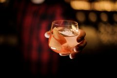Barman die heerlijke James Cook-cocktail in het glas met oranje schil dienen royalty-vrije stock foto