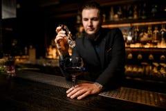 Barman die ijsblokje in alcoholcocktail zetten royalty-vrije stock afbeeldingen