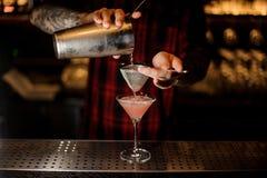 Barman die Kosmopolitisch van een schudbeker pourring aan een glas stock afbeeldingen