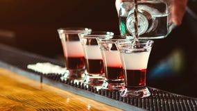 Barman die sterke alcoholische drank gieten in kleine glazen op bar Rode schoten bij de nachtclub De tijd van de partij Het barma stock fotografie