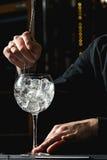 Barman die uit Cocktailglas koelen royalty-vrije stock afbeelding