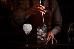 Barman die uit Cocktailglas koelen die ijs mengen met een lepel royalty-vrije stock afbeeldingen