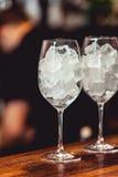 Barman die uit cocktailglas met ijs koelen stock afbeelding