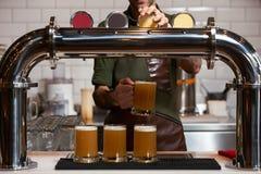 Barman die vers bier giet in het bierglas bij barteller, close-up stock afbeelding