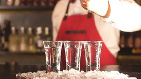 Barman die wat ijs zetten in schot berijpte glazen op een houten teller stock videobeelden