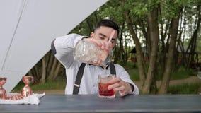 Barman dodaje alkohol w soku z lodem na baru kontuarze, barman przygotowywa chłodniczego koktajl z lodem, wydarzenie usługa zdjęcie wideo