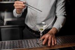Barman dodaje oliwki w Martini szkło z alkoholicznym dink fotografia royalty free