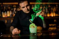 Barman dodaje szkło z wysuszoną pomarańcze i zamraża uwędzonego cynamon z pincetami zdjęcie stock