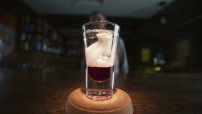 Barman dodaje zaskamla sirop płatowaty strzał z czerwonym trunkiem i dżinem w zwolnionym tempie, robi koktajlom w barze, alkoh zbiory