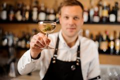 Barman holding a glass filled with alcoholic drink with olives Stock Photo