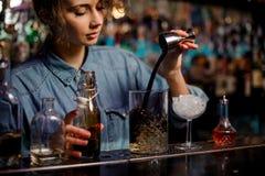 Barman dziewczyna nalewa pomiarowego szkła filiżanka z kostka lodu brązu alkoholicznego napój od stalowej osadzarki obraz stock