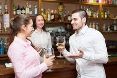 Barman et deux clients au compteur photos stock
