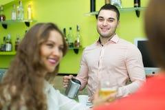 Barman et femmes de sourire à la barre Photographie stock