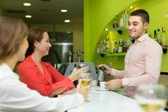 Barman et femmes de sourire à la barre Photos stock