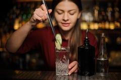 Barman féminin faisant un cocktail frais avec le genièvre et le concombre image stock