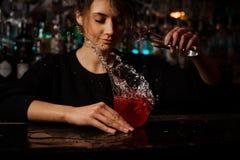 Barman féminin jetant à la position rouge en verre de cocktail sur le compteur de barre un glaçon avec l'éclaboussure photo libre de droits