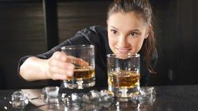 Barman féminin joyeux souriant regardant la lumière par un verre de vin Fille attirante au sourire de compteur de barre lent banque de vidéos