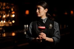 Barman féminin professionnel servant un cocktail cramoisi lisse dans le verre avec un bourgeon rose un rose de décor image stock
