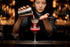 Barman féminin professionnel versant un cocktail cramoisi lisse au travers du tamis au verre photographie stock